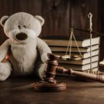 Teddy bear on desk with gavel and scale